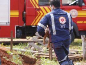 Socorrista do Samu corre com a vítima nos braços durante resgate.