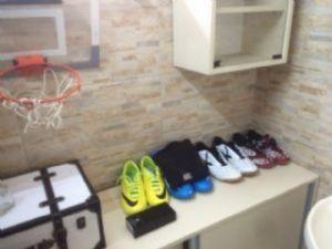 Tênis esportivos e uma pequena cesta de basquete encontrados em cela.
