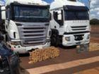 Pilhas de tabletes de cocaína em frente às duas carretas apreendias pela PRF hoje em Dourados.